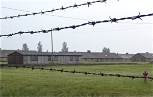 A row of barracks past the barbed wire at Auschwitz-Birkenau
